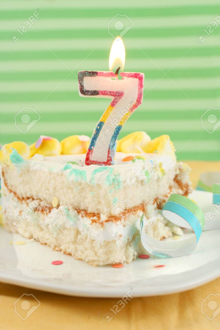 Slice Of Seventh Birthday Cake With Lit Candle Confetti And Ribbon Shallow Depth