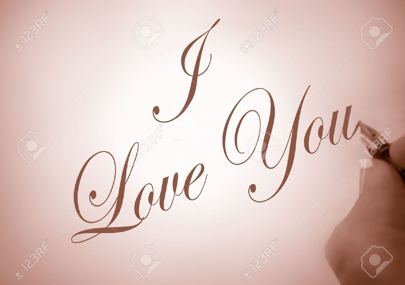 Person writing i love you in calligraphy in sepia tone stock photo