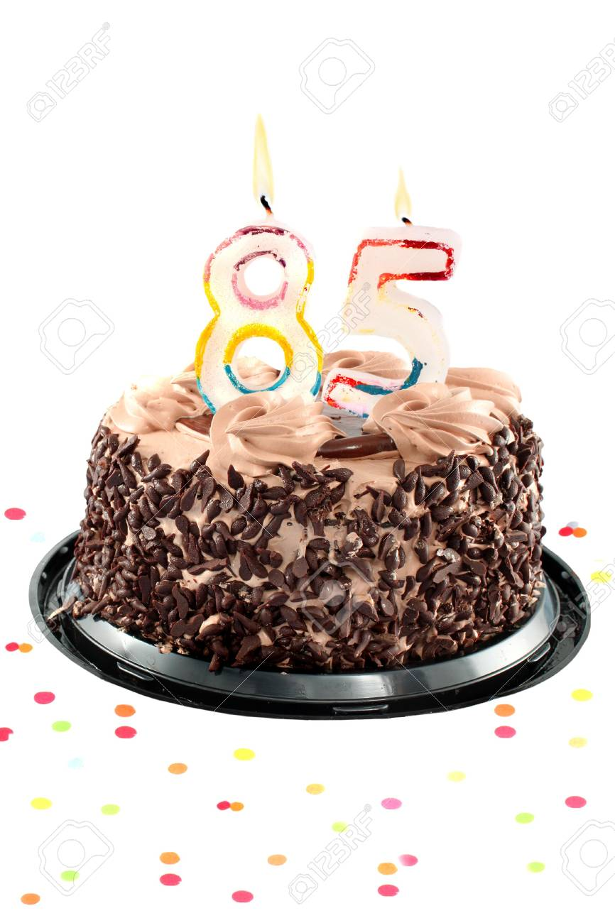 Chocolate Birthday Cake Surrounded By Confetti With Lit Candle