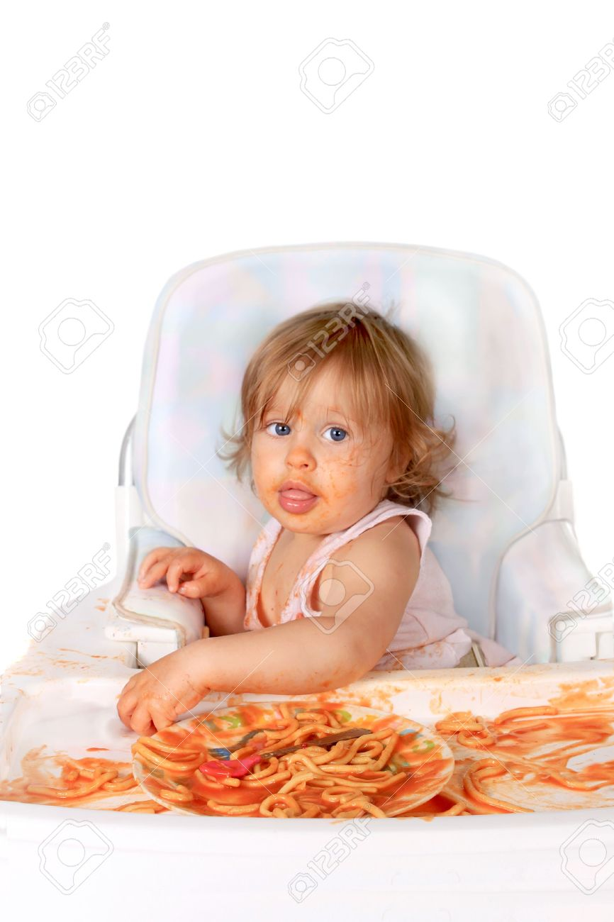 Young blue eyed baby girl making a mess with spaghetti in tomato sauce on a white background Stock Photo - 7528414