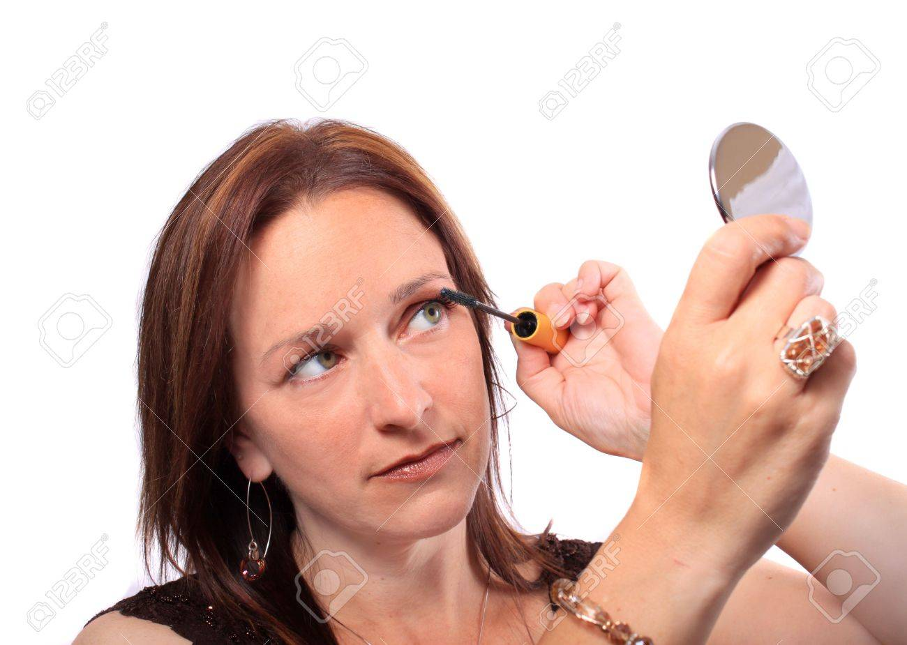 woman holding hand mirror. woman holding hand mirror applies mascara to eyelashes stock photo - 7837521 i