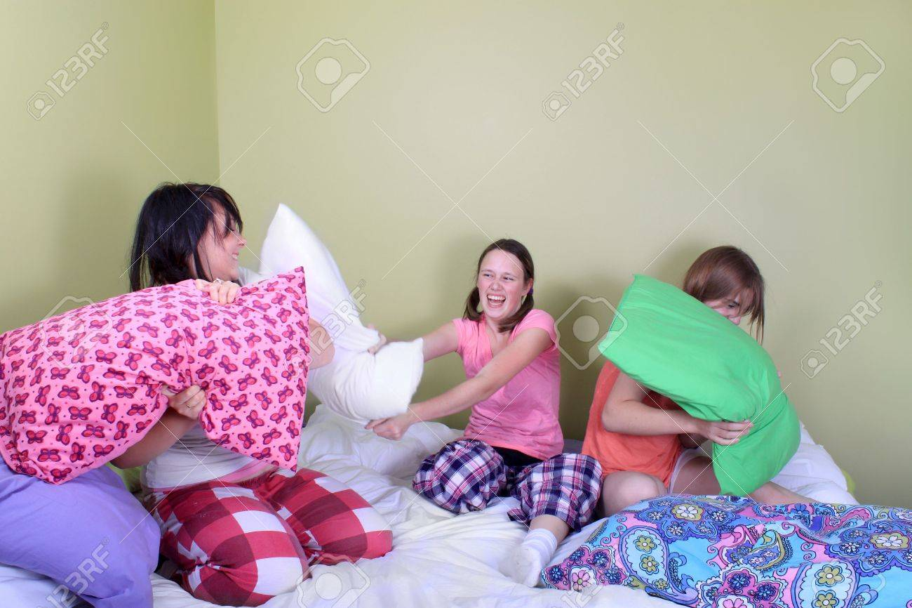 Three teenage girls in their pajamas with pigtails or braids having a pillow fight on a bed at a sleepover Stock Photo - 7937234