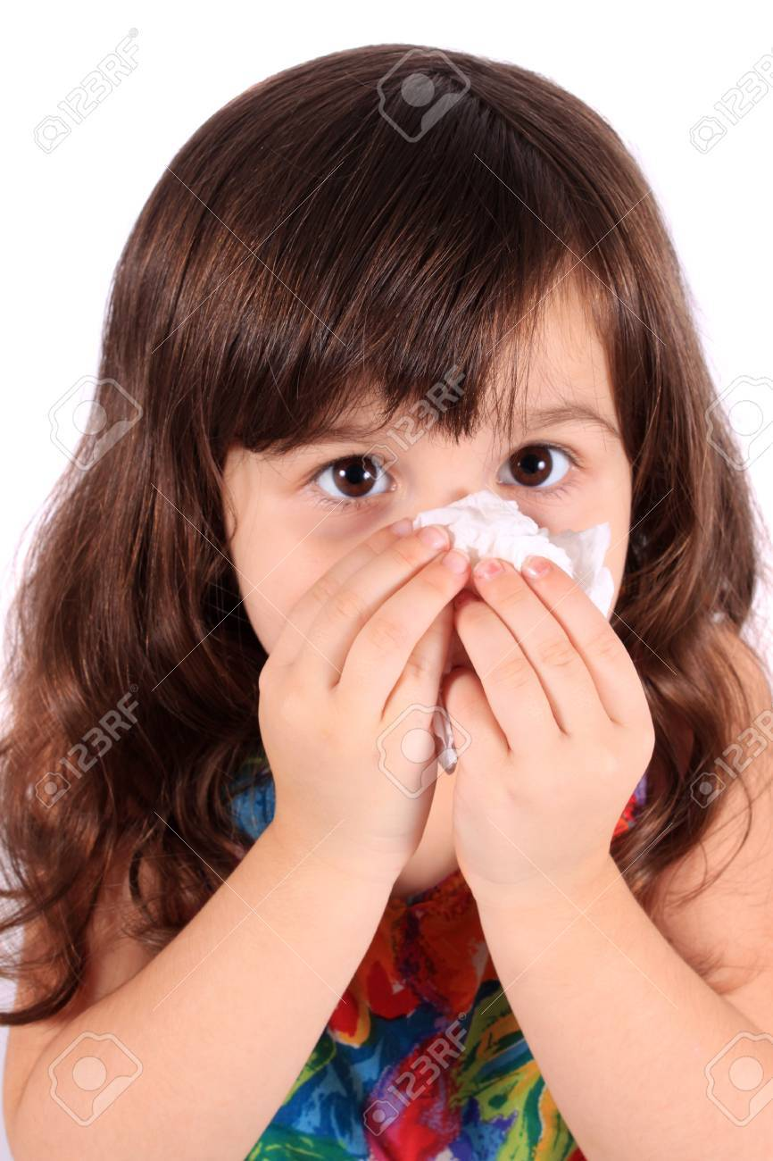 Little three year old girl having the sniffles and wiping her nose with tissue from being sick or allergies - 8244698