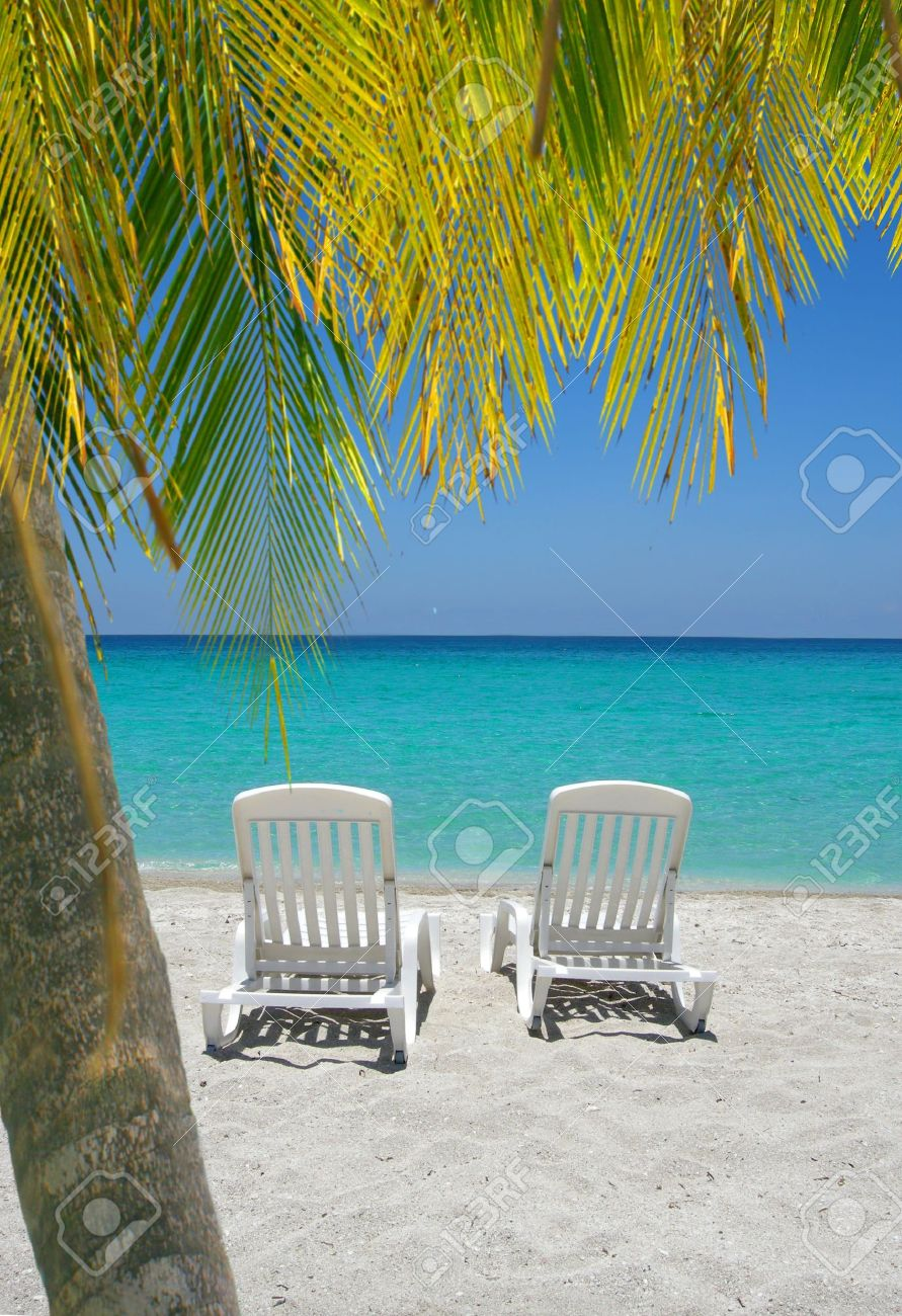 Beach with chairs - Empty Tropical Beach Chairs On Sand At Shoreline With Palm Trees In Front In The Caribbean
