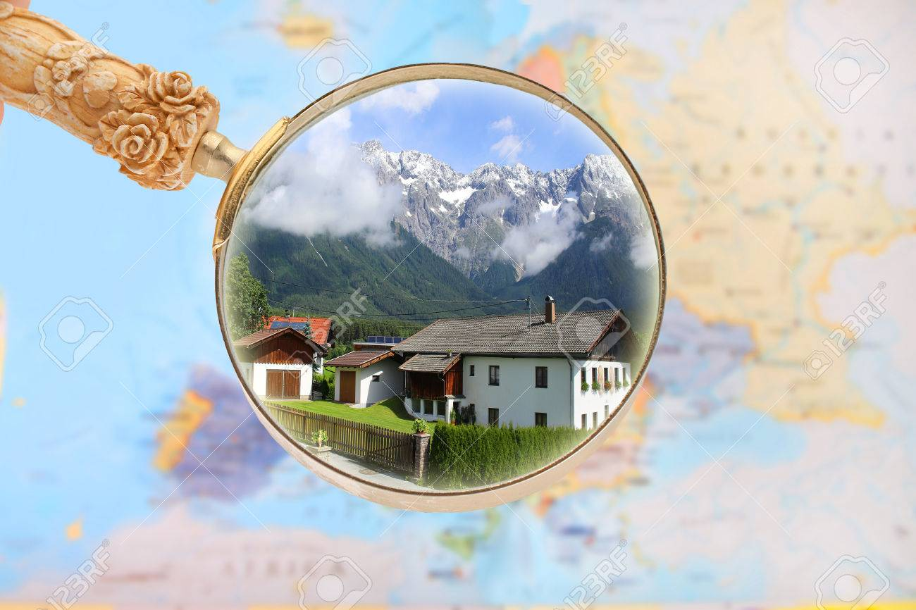 Map of Europe with magnifying glass looking in on a house with..