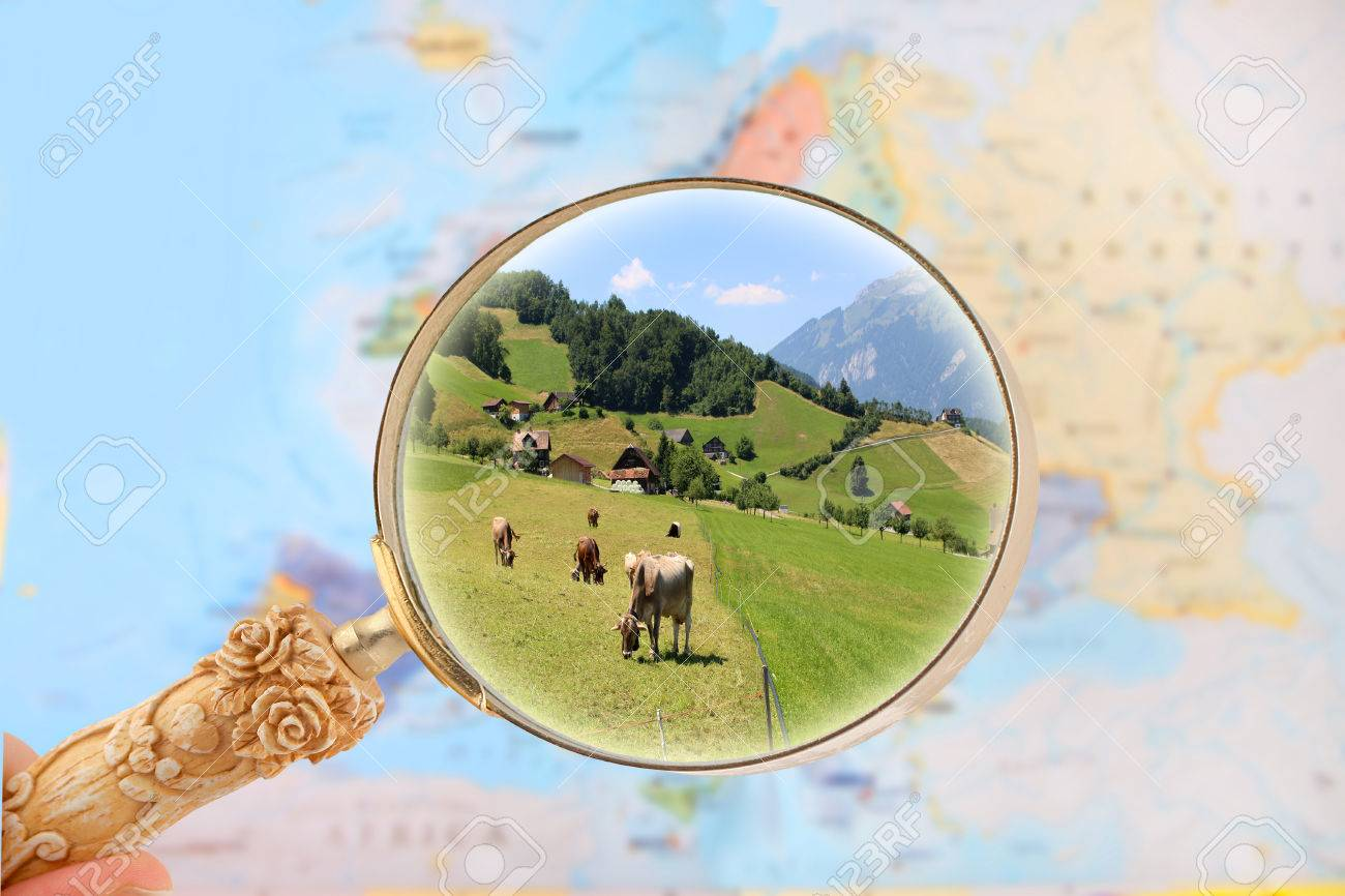 stock photo zooming on a map of europe with magnifying glass looking in on cattle in a farm switzerland europe