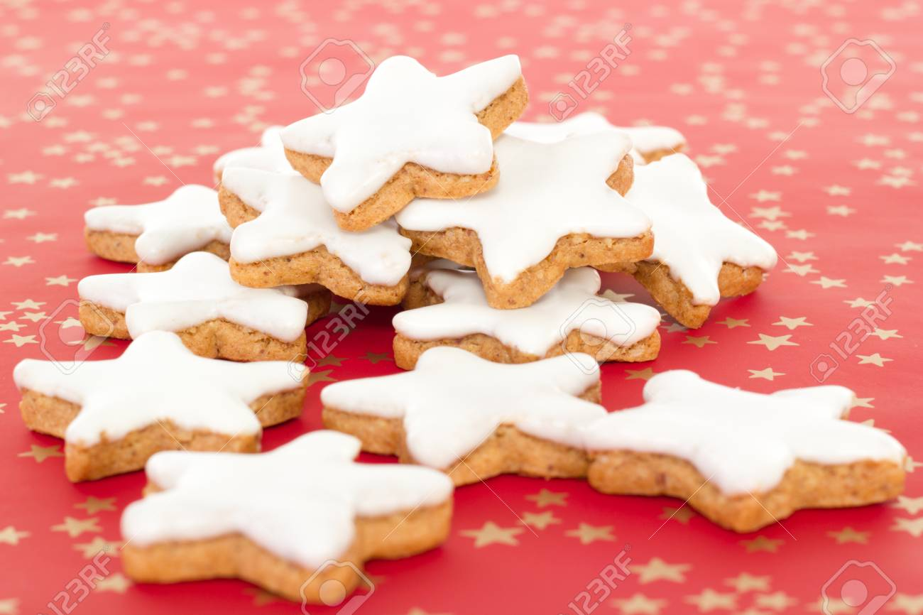 Many Star Shaped Cinnamon Biscuits On Red Background With Golden