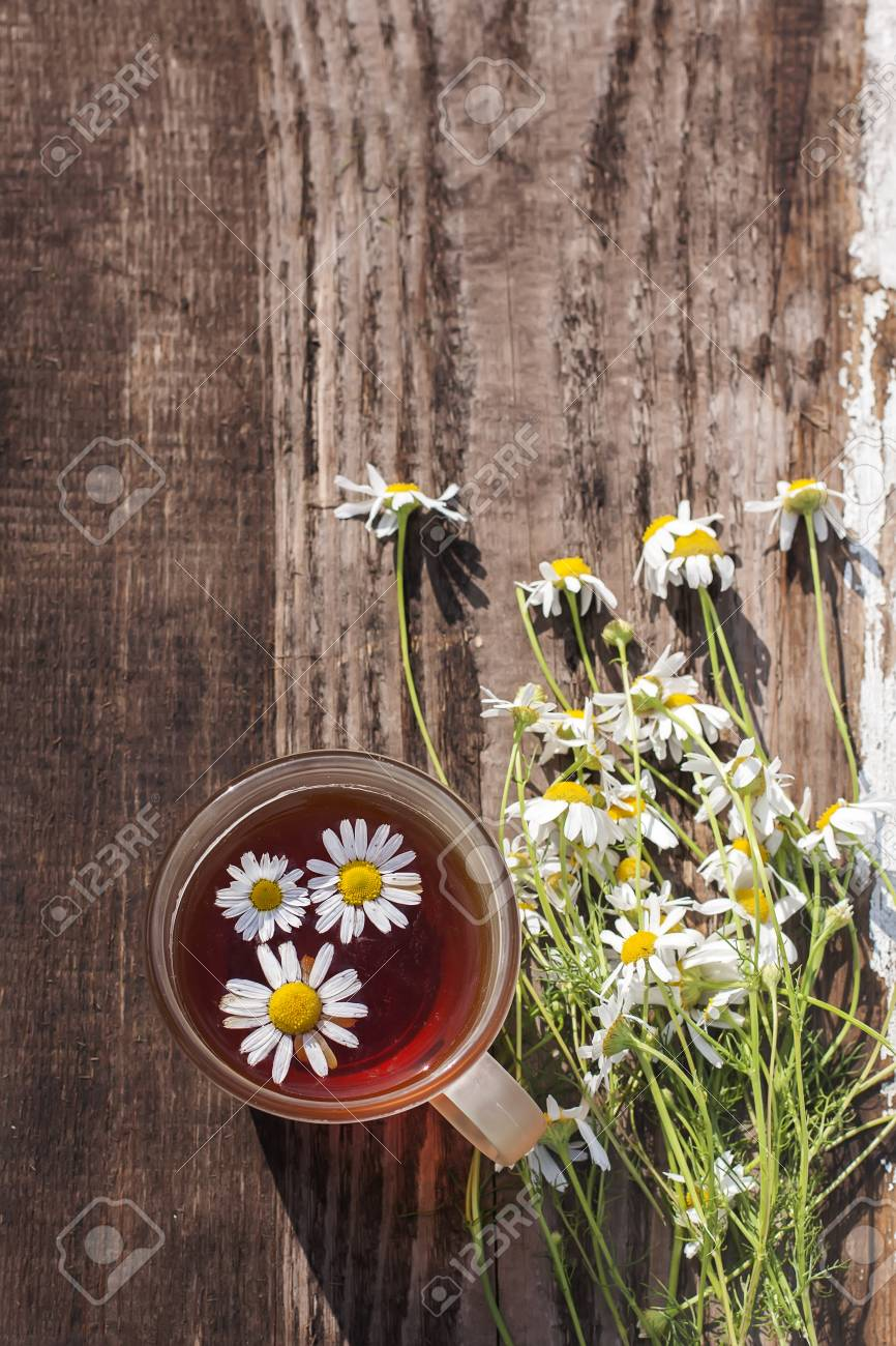 cup of chamomile tea with chamomile flowers, old wood table background - 42444838