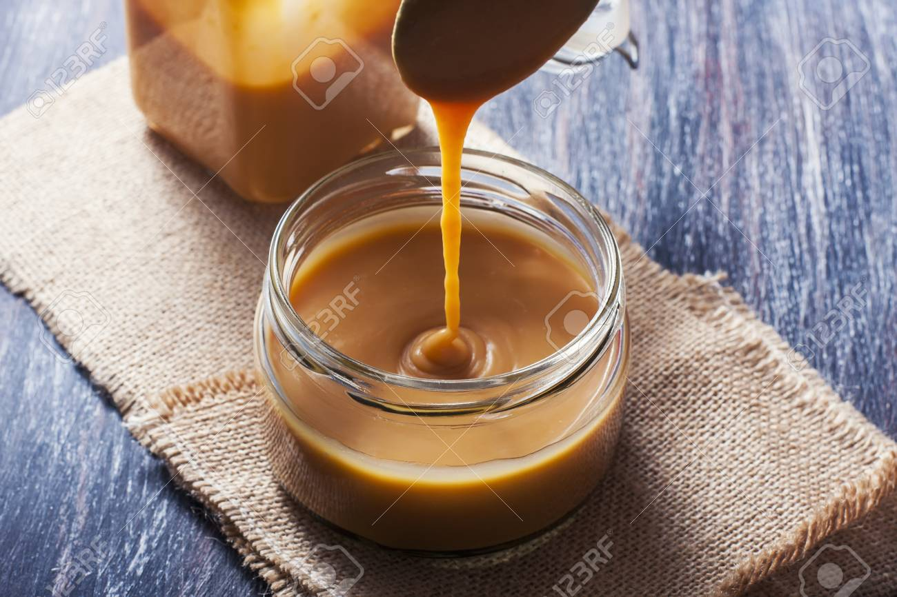 Homemade caramel sauce in a glass jar. Selective focus - 55151296