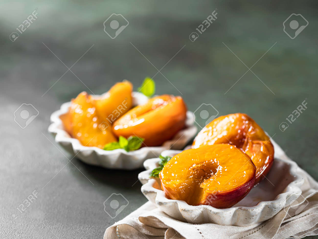 Caramelized peaches with honey, with mint leaves on a concrete background with shadows. Summer dessert. - 171666899