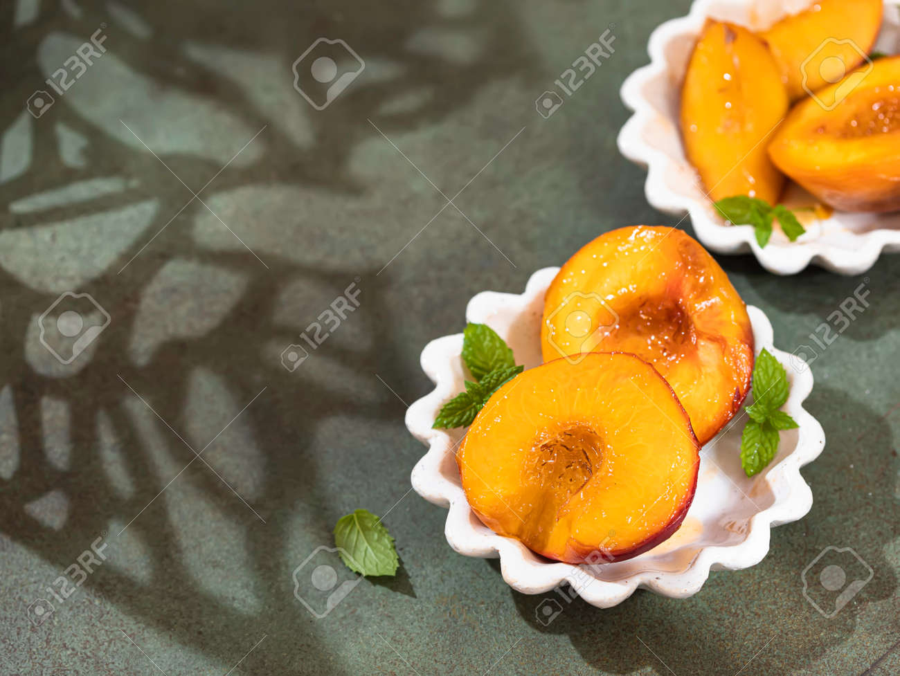 Caramelized peaches with honey, with mint leaves on a concrete background with shadows. Summer dessert. - 171666919