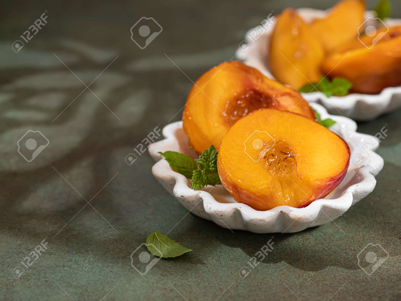 Caramelized peaches with honey, with mint leaves on a concrete background with shadows. Summer dessert. - 171666674