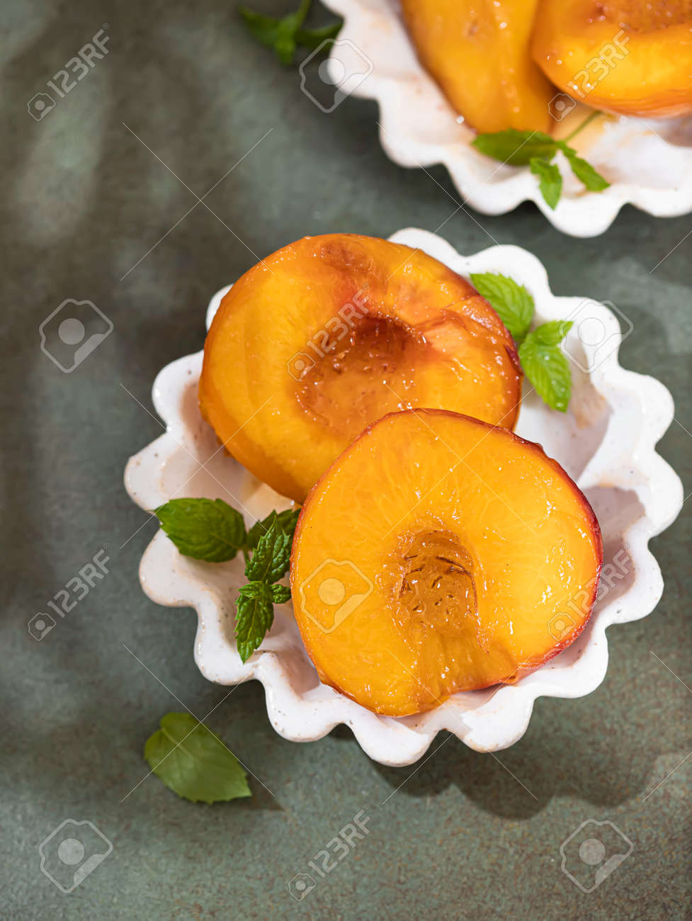 Caramelized peaches with honey, with mint leaves on a concrete background with shadows. Summer dessert. - 171666840