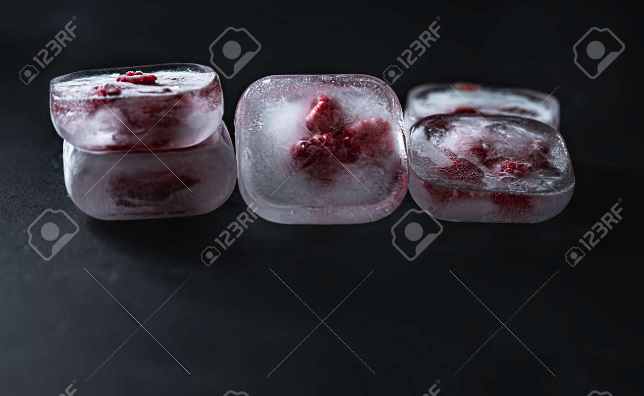 Raspberry frozen in the ice cube on black background. Fresh healthy summer eating. - 171671488