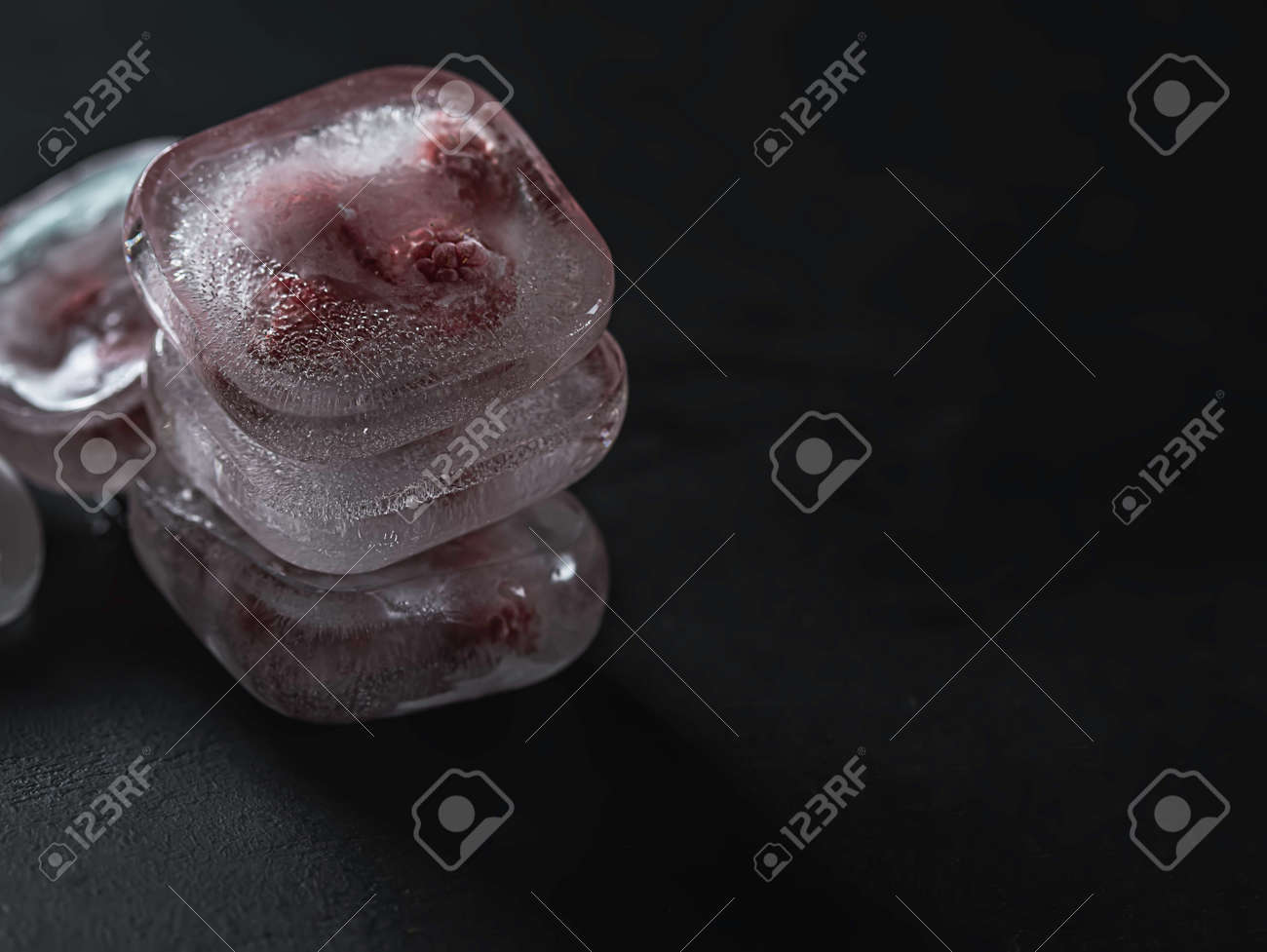 Raspberry frozen in the ice cube on black background. Fresh healthy summer eating. - 171707458