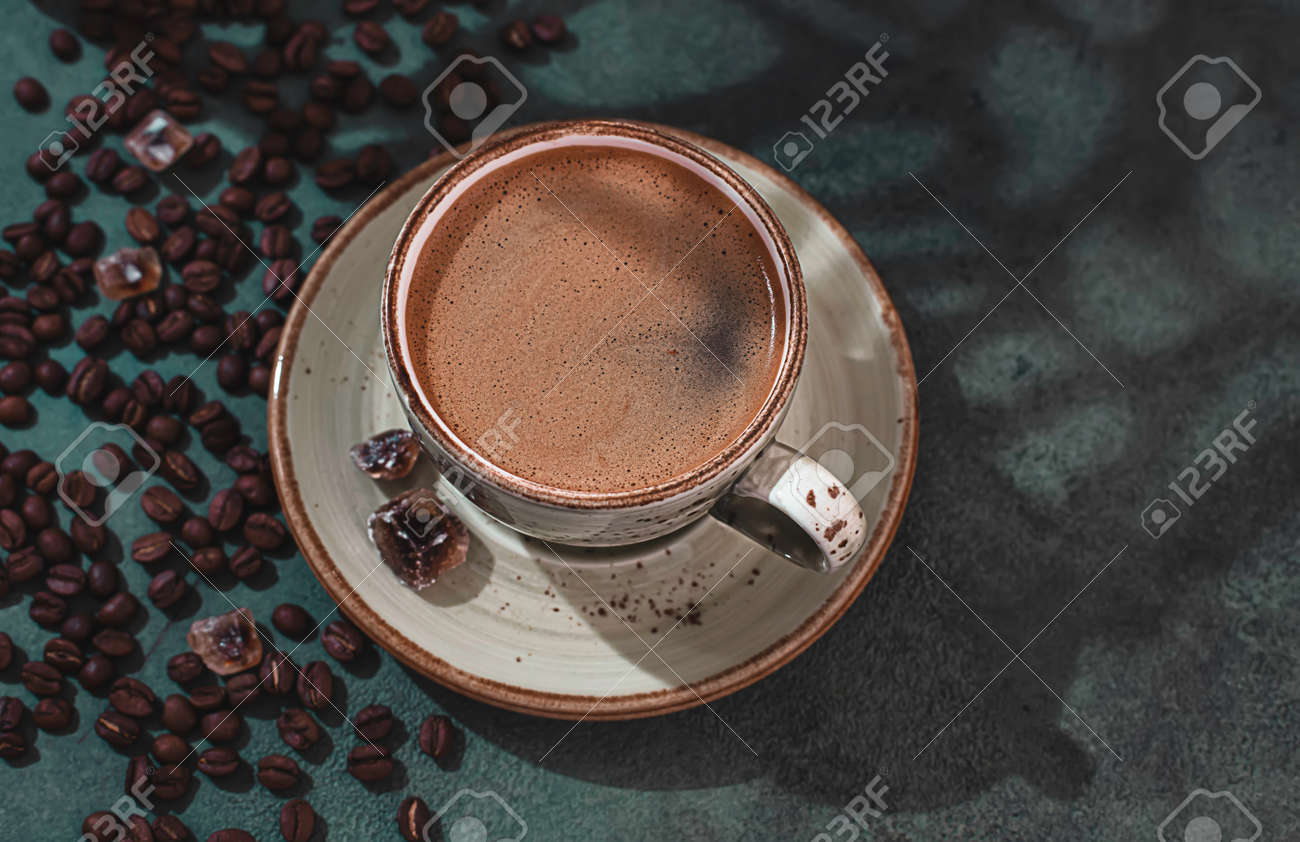 Fragrant strong coffee and coffee beans on a dark green concrete background. The concept of hot drinks. Copy space for your text - 171872360