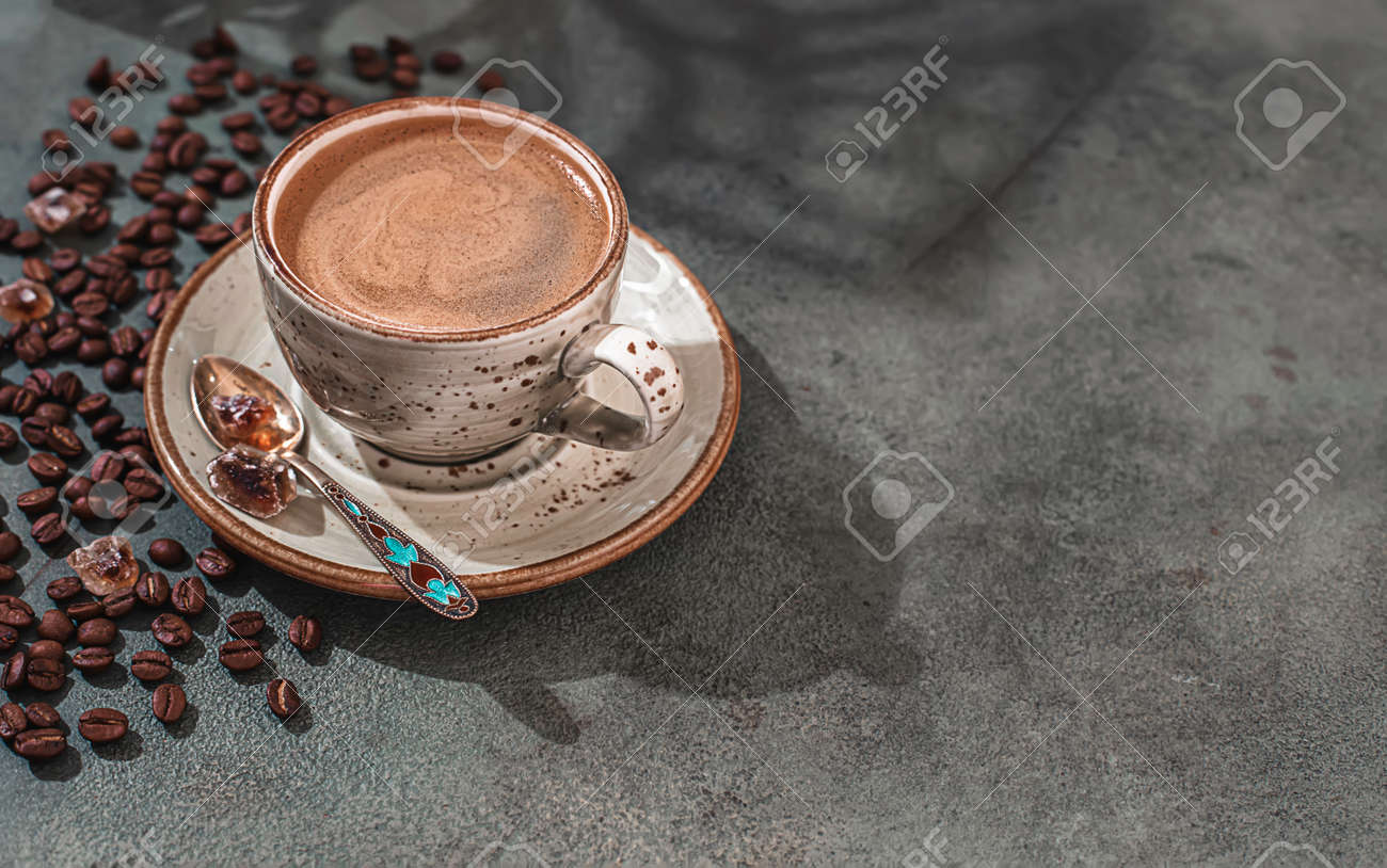 Fragrant strong coffee and coffee beans on a dark green concrete background. The concept of hot drinks. - 171765672