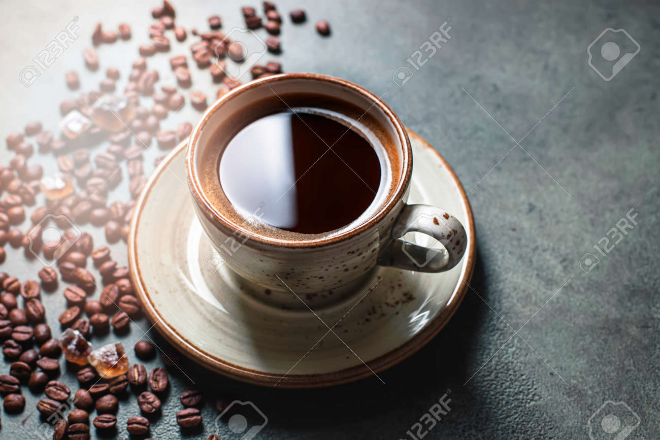 Fragrant strong coffee and coffee beans on a dark green concrete background. The concept of hot drinks. - 171765831