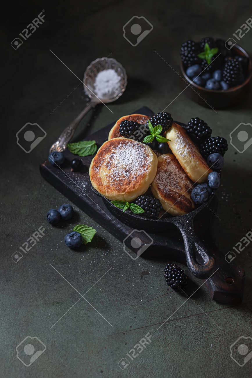 Curd pancakes or syrniki with fresh berries on a concrete background. Ukrainian, Russian cuisine sweet food. Delicious healthy breakfast. Selective focus - 171890446