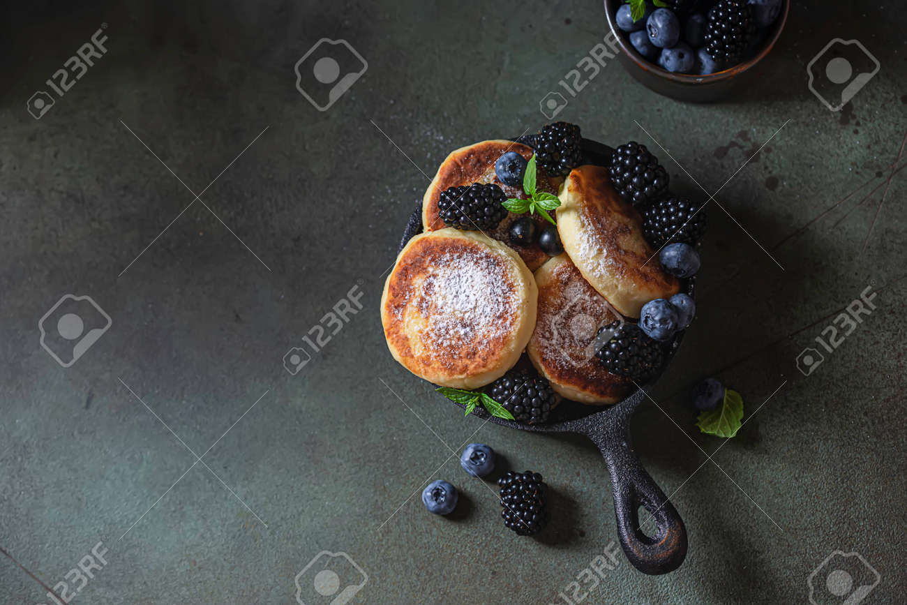 Curd pancakes or syrniki with fresh berries on a concrete background. Ukrainian, Russian cuisine sweet food. Delicious healthy breakfast. Selective focus - 171890450