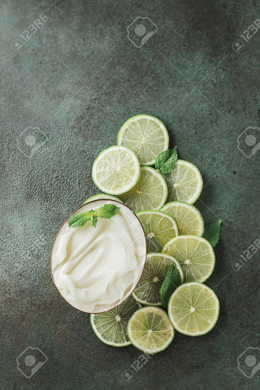Jar with cosmetic product with lime and mint halves on green concrete. Natural citrus cosmetics with vitamin C. Copy space. - 171871957
