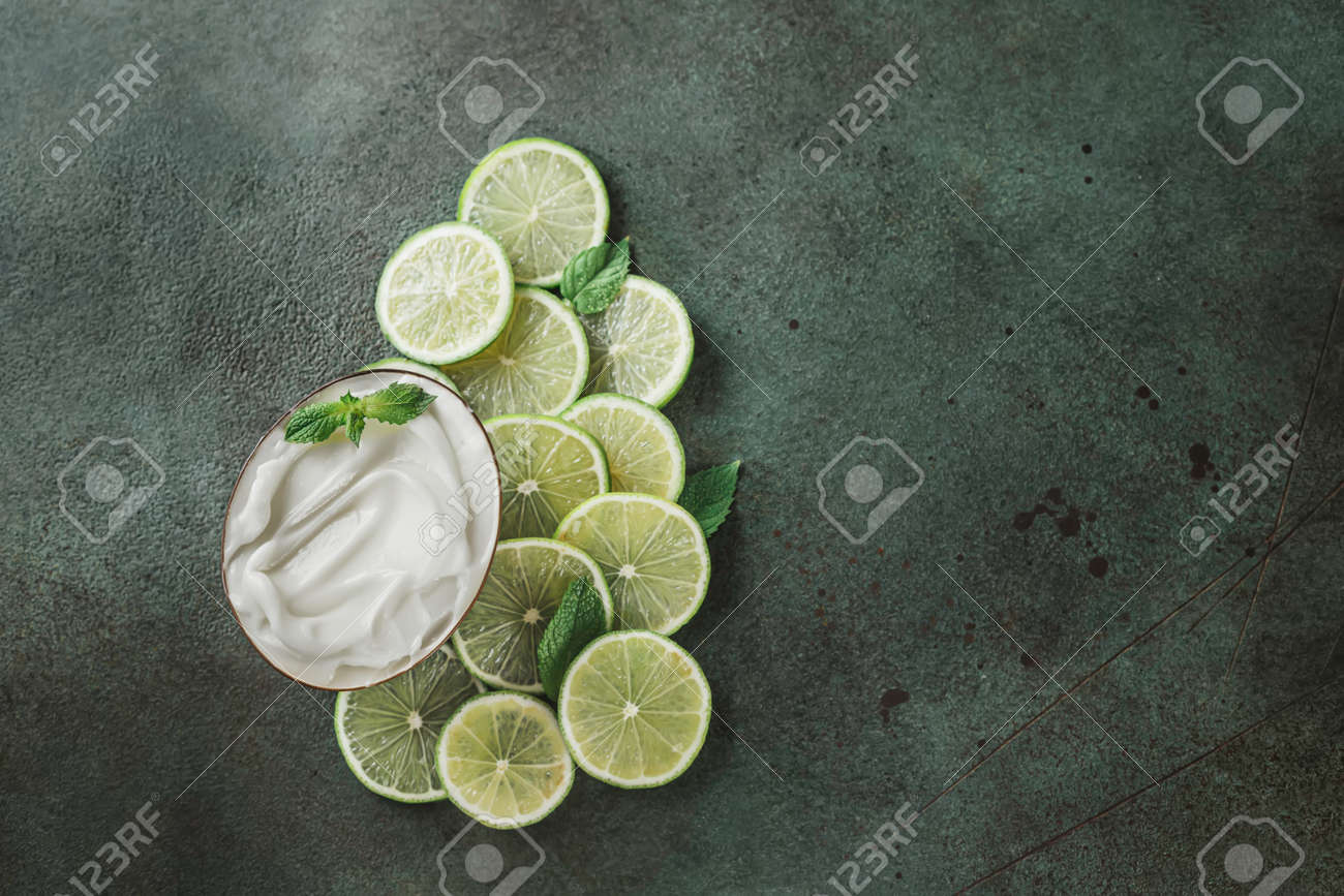 Jar with cosmetic product with lime and mint halves on green concrete. Natural citrus cosmetics with vitamin C. Copy space. - 171871487