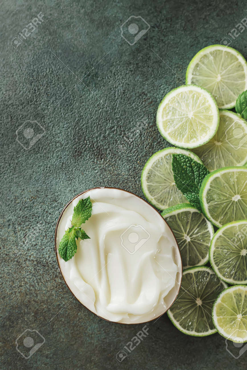 Jar with cosmetic product with lime and mint halves on green concrete. Natural citrus cosmetics with vitamin C. Copy space. - 171871163