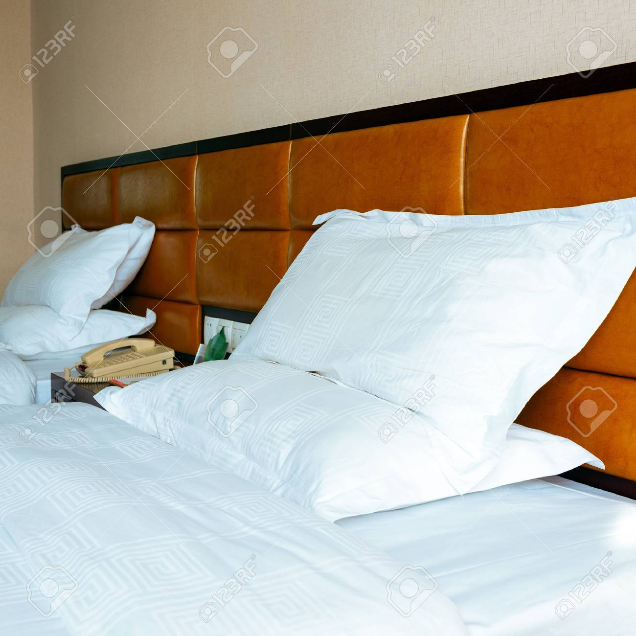 The beds, white linens and pillows Stock Photo - 21430993