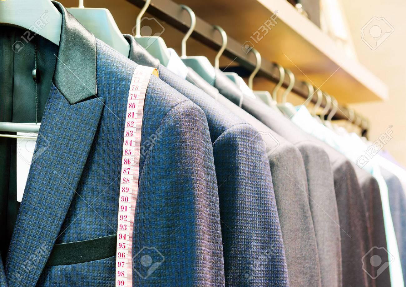 Row of men's suits hanging in closet. - 38293838