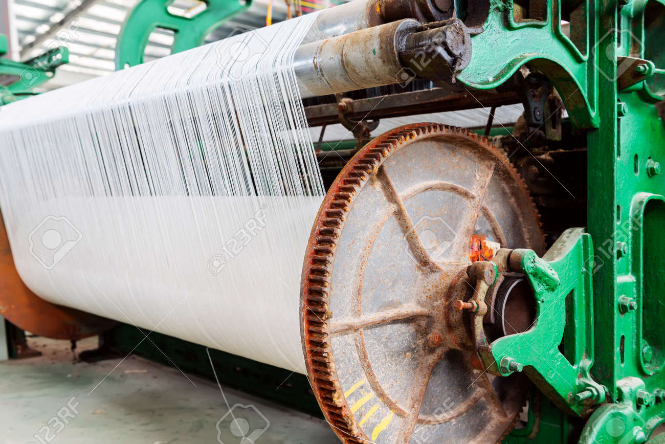 A row of textile looms weaving cotton yarn in a textile mill. - 62599233