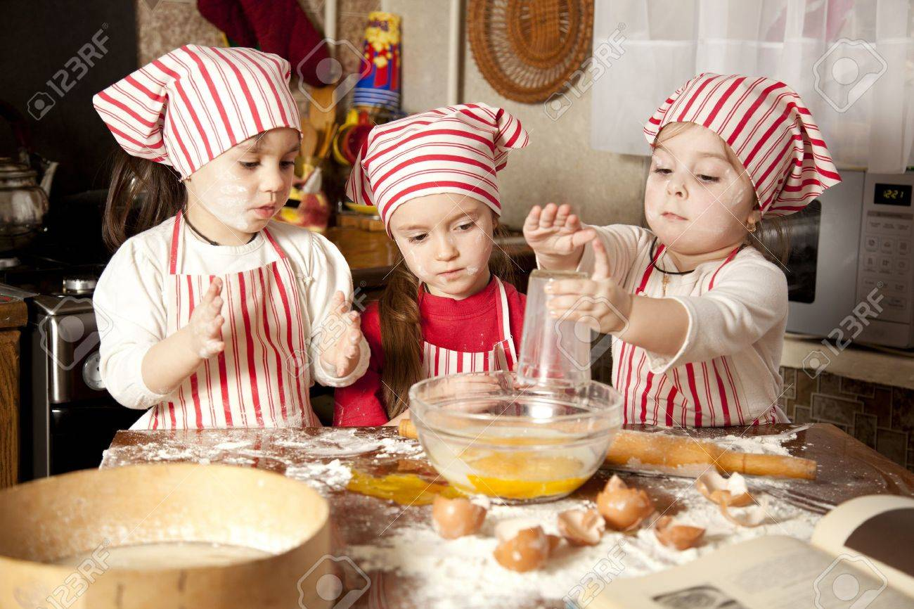 Three little chefs enjoying in the kitchen making big mess  Little girls making bread in the kitchen Stock Photo - 12975123