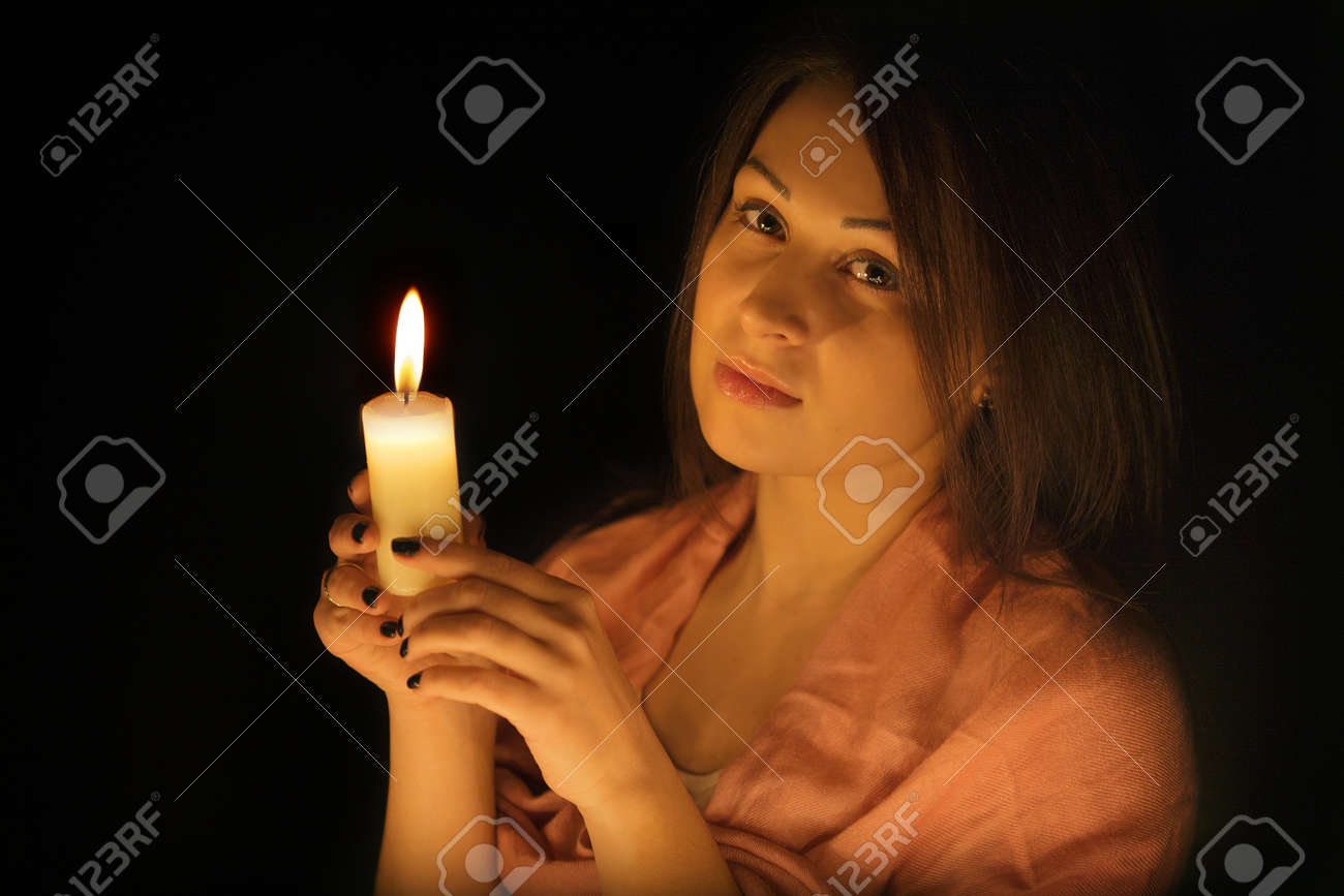 Beautiful girl with a candle in the dark Stock Photo - 14748896