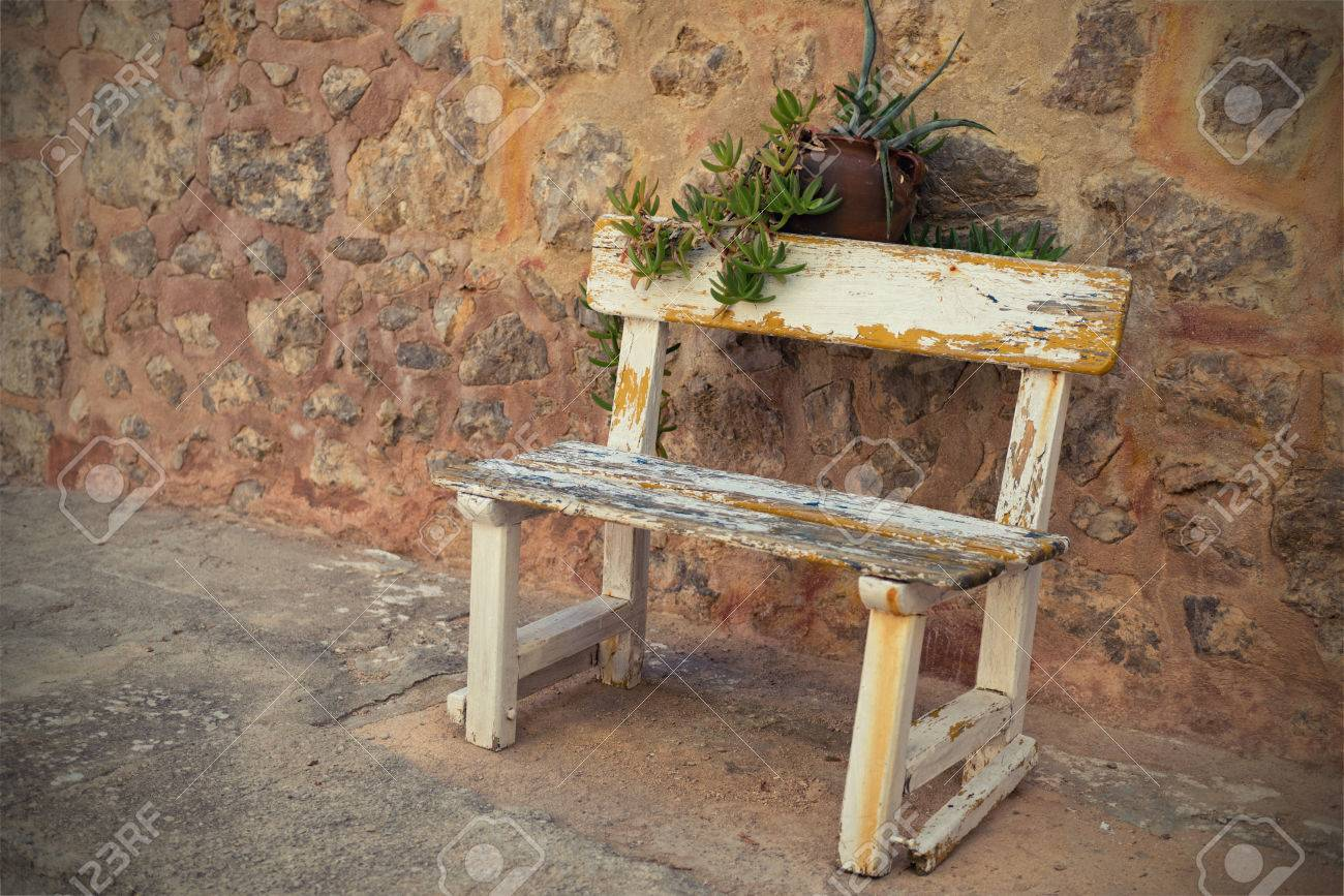 Rustic outdoor wood bench - Empty Rustic Wooden Outdoor Cottage Bench Painted White Against Wall Stock Photo 27335756