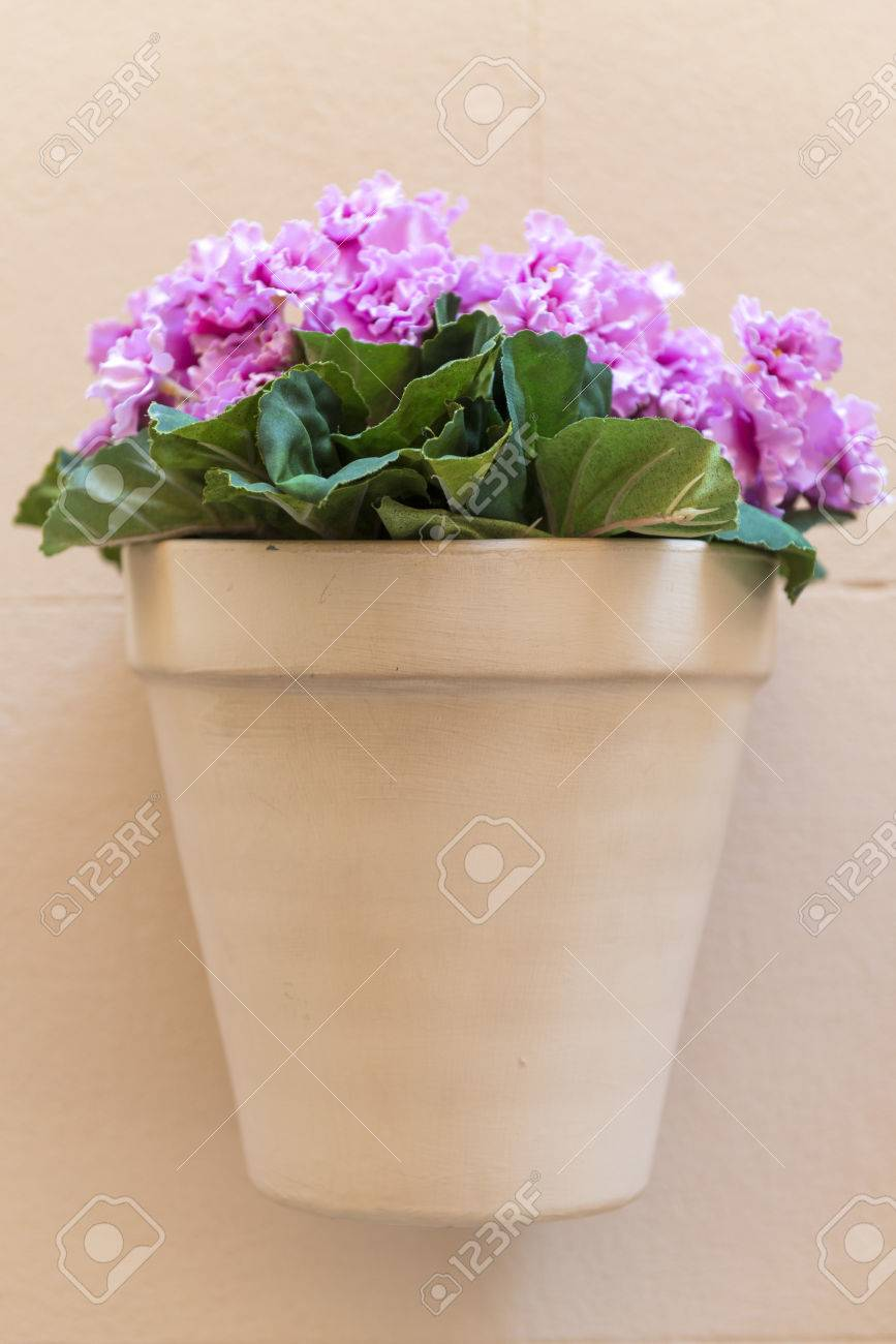 Flower Pot With Pink Flowers Hanging On A House Wall Stock Photo
