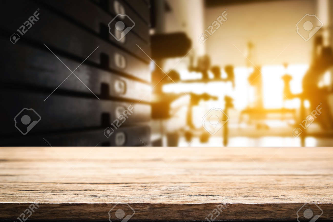Wooden desk space over fitness gym and man open hand to empty desk. For product display montage. Business presentation. - 65840374