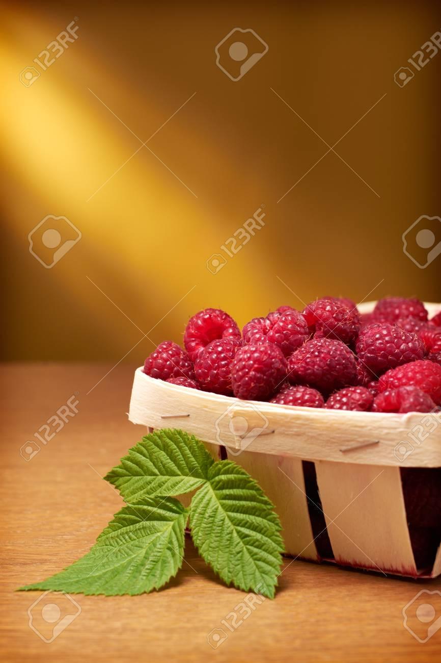 Fresh raspberries in the basket on yellow background Stock Photo - 11136281