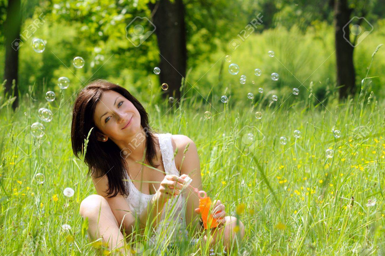 Portrait of young girl inflating soap bubbles on green meadow Stock Photo - 13809754