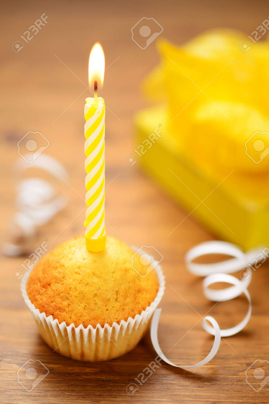 Birthday Cake Or Muffin With A Yellow Candle On Wooden Table Stock Photo