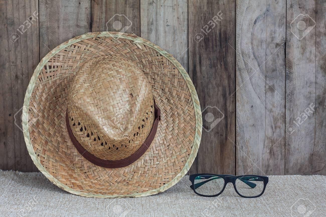 807492501ac15 Foto de archivo - Sombrero de mimbre con los anteojos sobre tela marrón  apoyarse contra el fondo de pared de madera