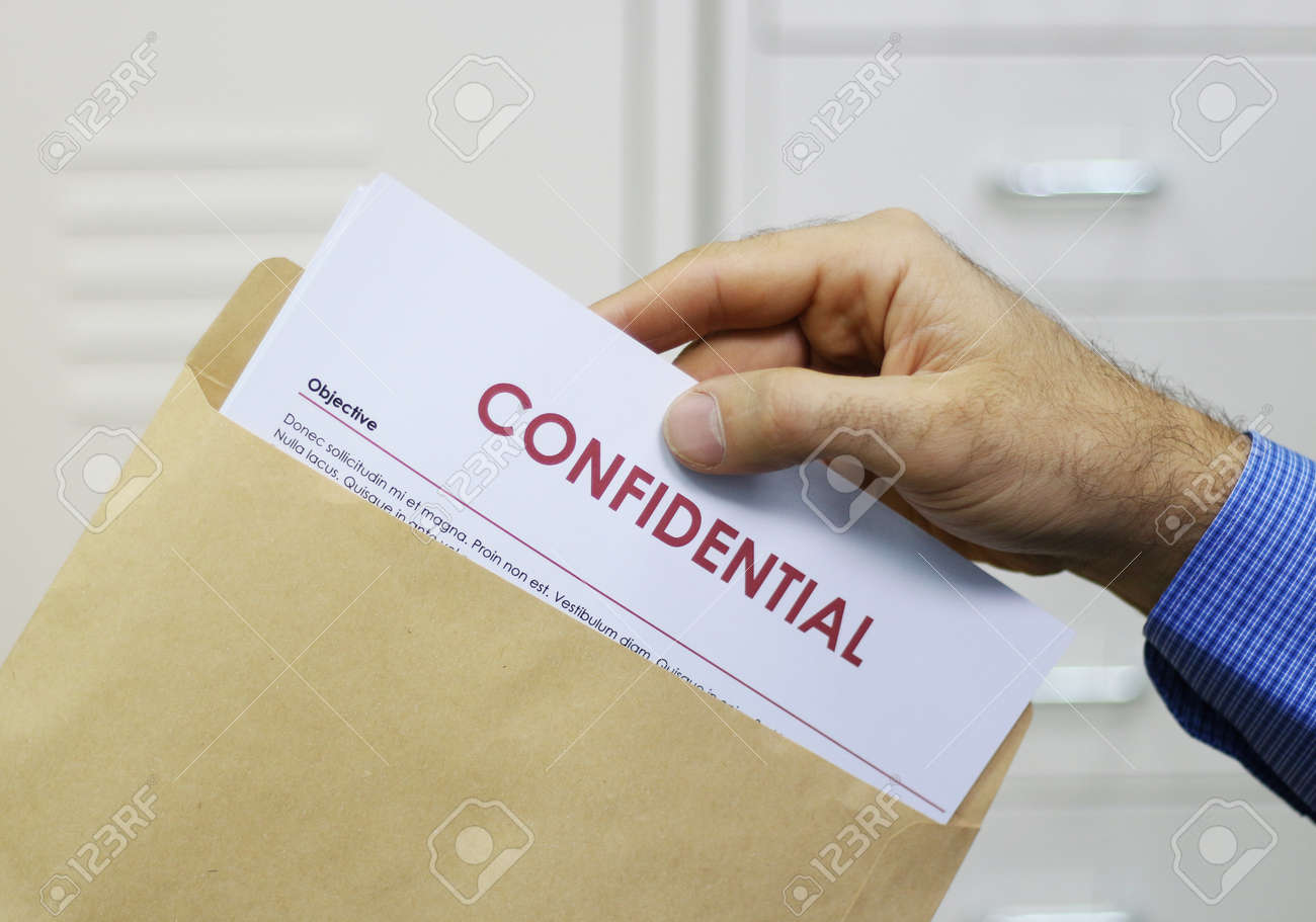 Cropped view image of a man handling confidential documents placing them inside a brown manilla envelope for mailing - 20911262