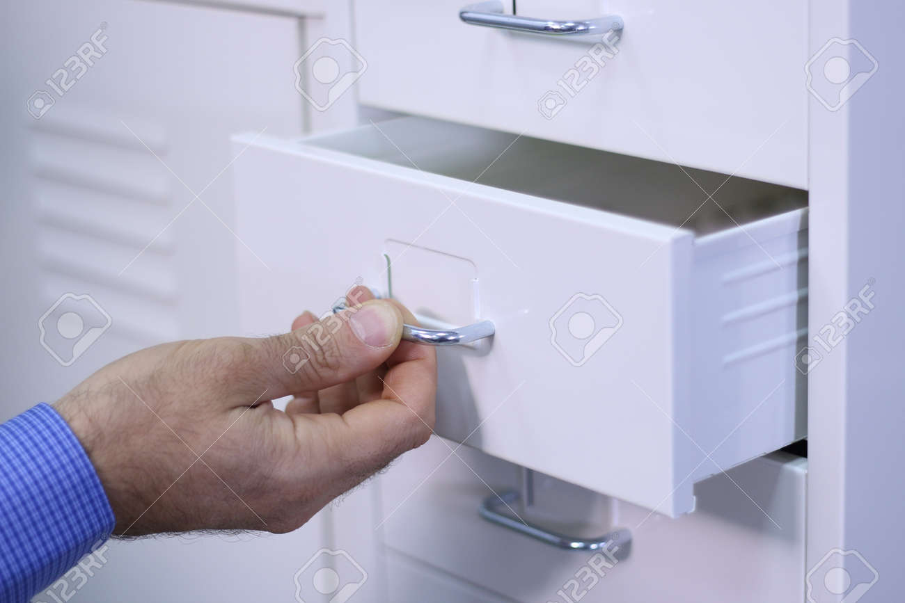 Cropped view image of a male hand opening a small drawer in a white cabinet Stock Photo - 17152629