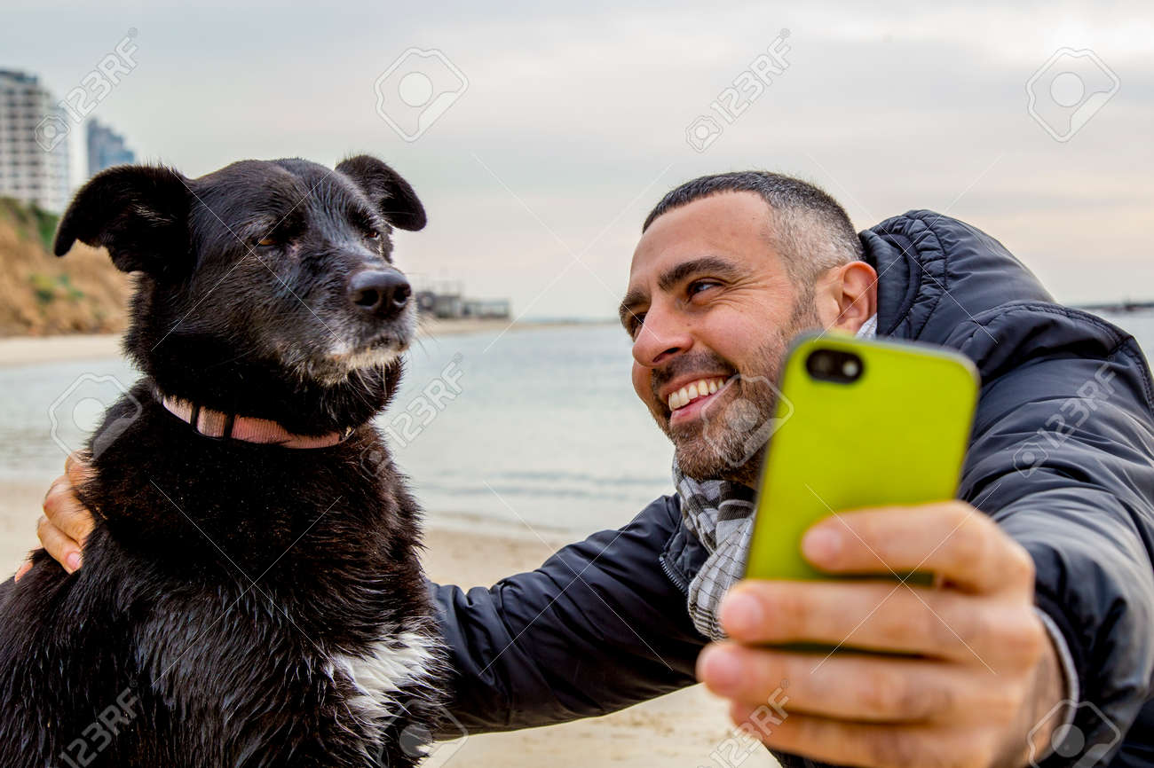 Man helping his grumpy dog firend to take a social media selfie image using a smartphone - 41498928