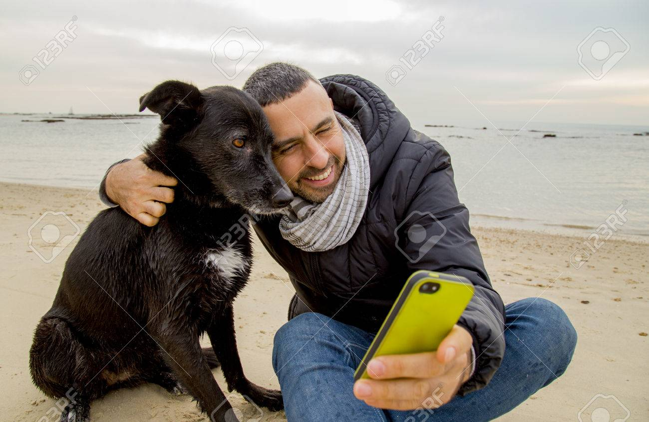 Man helping his dog making selfie image using a smartphone - 41499087
