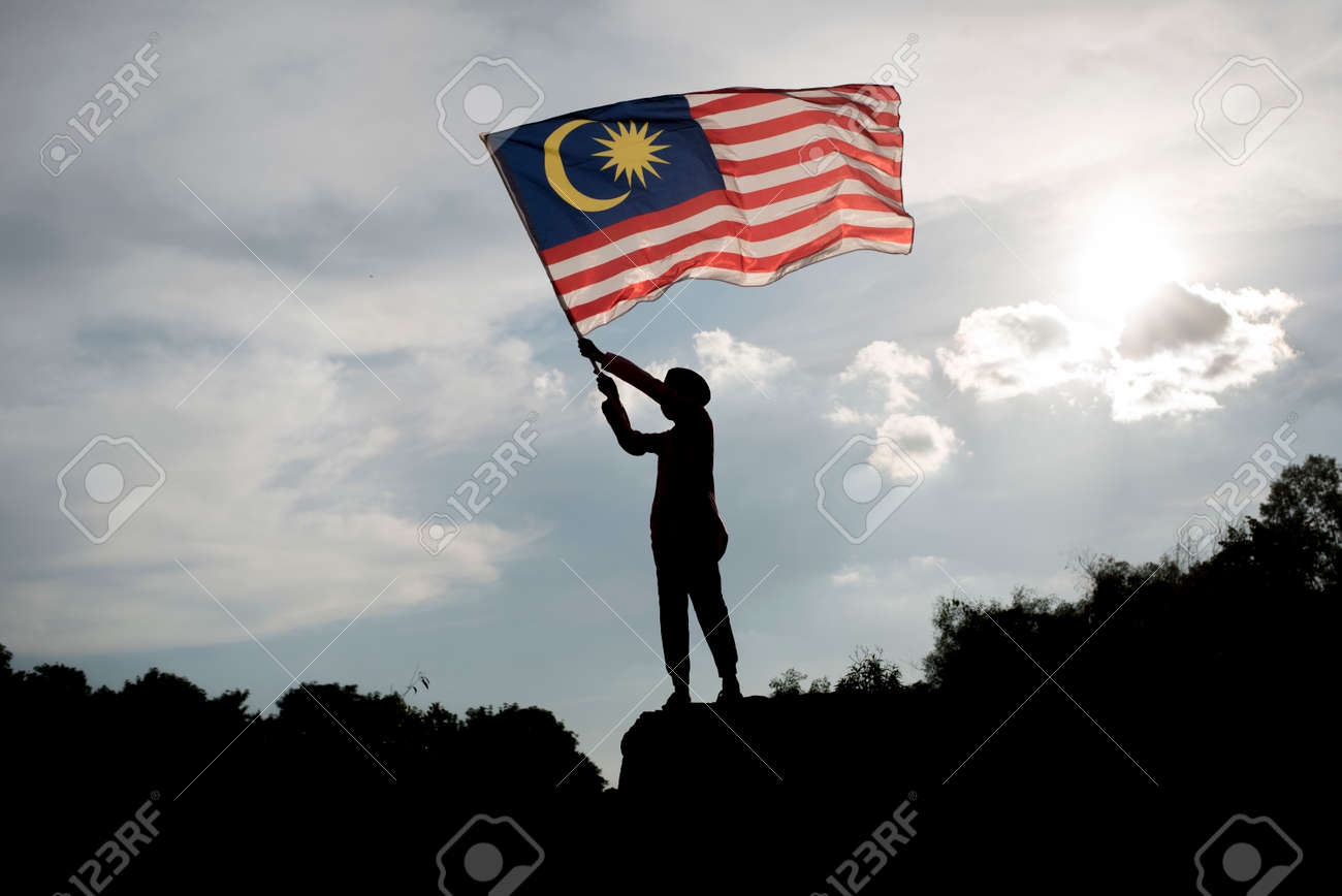 Silhouette of a boy holding the malaysian flag celebrating the Malaysia independence day - 83496653