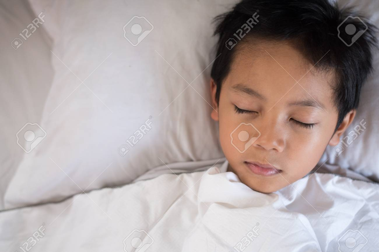 b6b64d9ba boy sleeping on bed with white sheet and pillow.asian kid fall asleep  daydreaming.