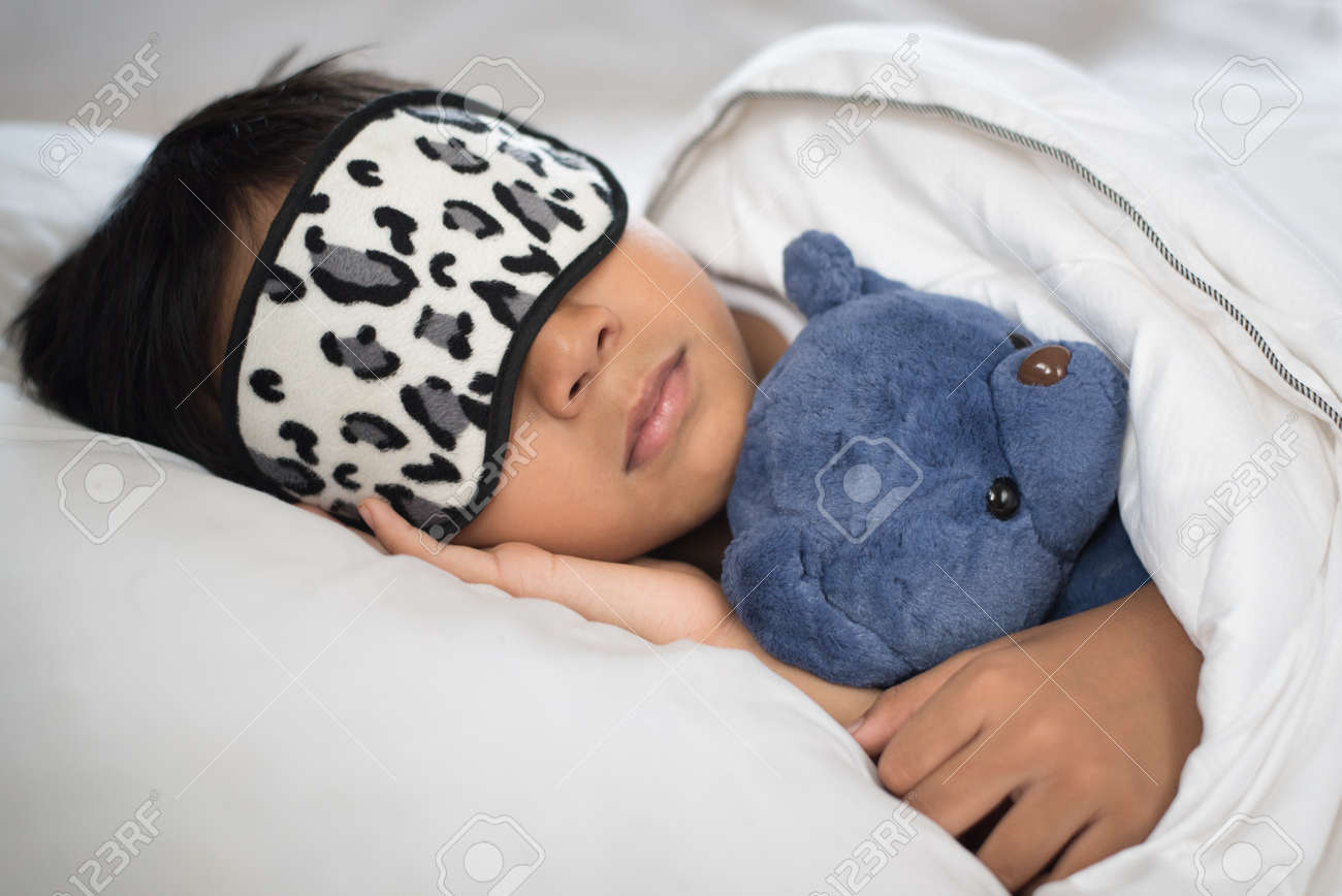 c5fb64a5a boy sleeping on bed with teddy bear white pillow and sheets wearing sleep  mask.boy
