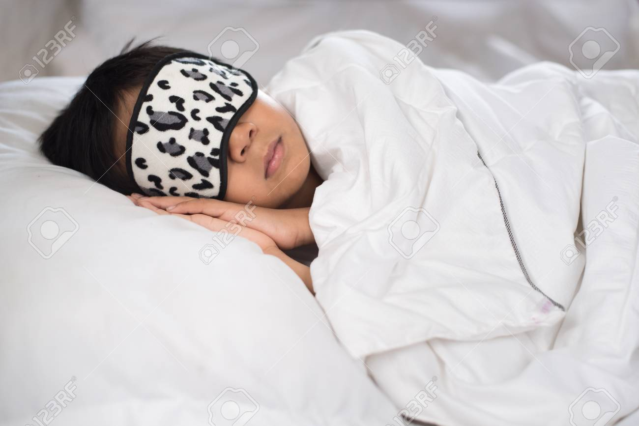 a0ad055f3 boy sleeping on bed white pillow and sheets with sleep mask.boy sleeping  peacefully.