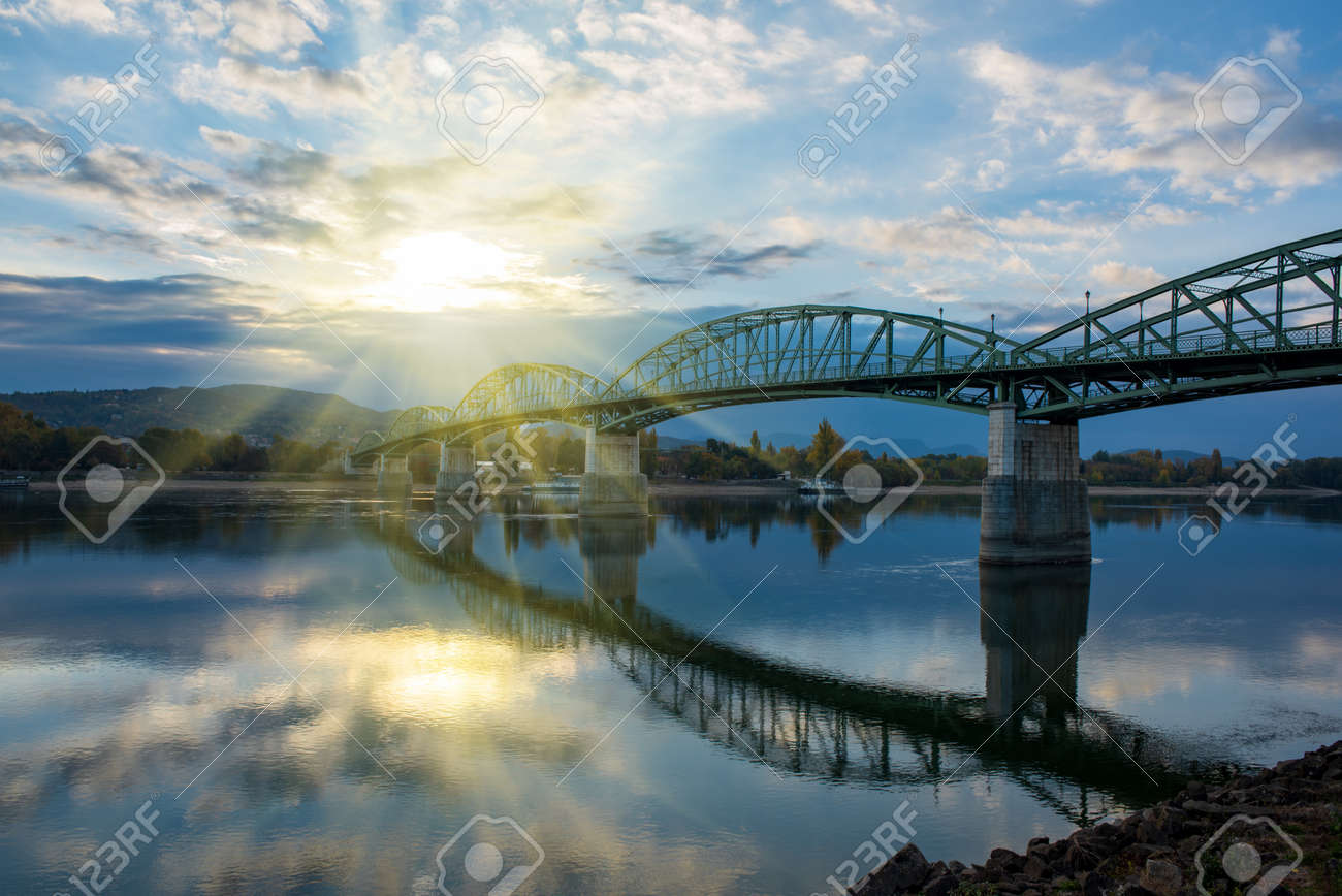 Amazing view of Maria Valeria bridge with reflection in Danube river on Slovak-Hungary border at sunrise. Esztergom, Hungary. Autumn morning. Travel destination - 120093312