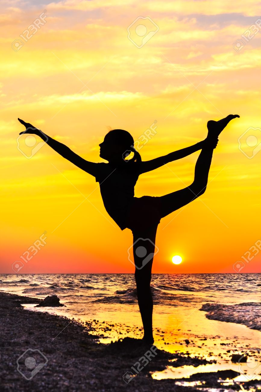 Silhouette Of A Girl In Yoga Pose On The Beach At Picturesque Sunset Stock Photo