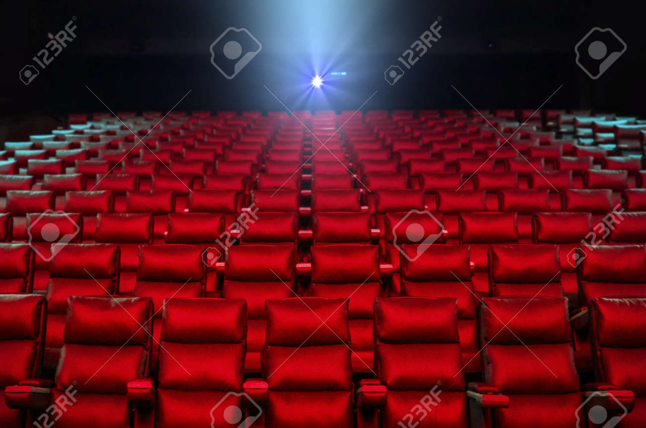 Red cinema seats with projector bright lights in background - 146681250